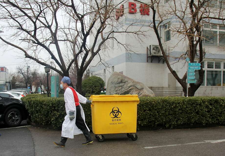 An employee pulls a container with medical waste at a Beijing hospital. Belief that the worst of the economic impact of the coronavirus is over has helped drive up oil prices. Photo: Roman Balandin / TASS / TNS