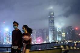 A couple wears face masks as a preventative measure against the COVID-19 coronavirus, as they walk along the promenade in Tsim Sha Tsui of Hong Kong on February 14, 2020. - The death toll from China's virus epidemic neared 1,400 on Friday with six medical workers among the victims, underscoring the country's struggle to contain a deepening health crisis.