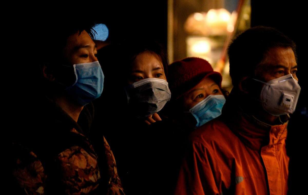 People wearing protective facemasks queue to order food from a stall in Shanghai on February 14, 2020. - Youan Hospital is one of twenty hospitals in Beijing treating coronavirus patients. Six health workers have died from the COVID-19 coronavirus in China and more than 1,700 have been infected, health officials said on February 14, underscoring the risks doctors and nurses have taken due to shortages of protective gear.