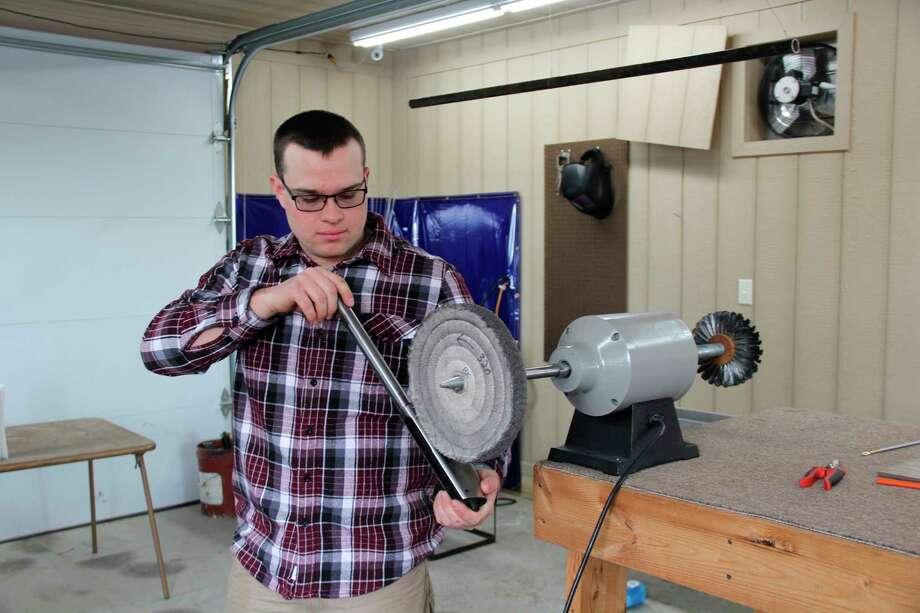 Brandon Krohn works on polishing the barrel of a rifle. Krohn opened up a small gunsmithing shop where he repairs and customizes firearms. (Robert Creenan/Huron Daily Tribune)