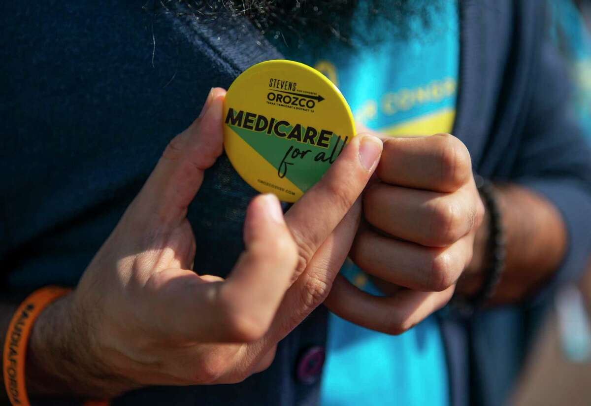Stevens Orozco puts on a button that pledges his desire to push for Medicare coverage for all people before walking door to door campaigning, Saturday, Feb. 8, 2020, in Houston's Heights area. Orozco is one of six candidates challenging Congresswoman Sheila Jackson Lee in the upcoming democratic primary.