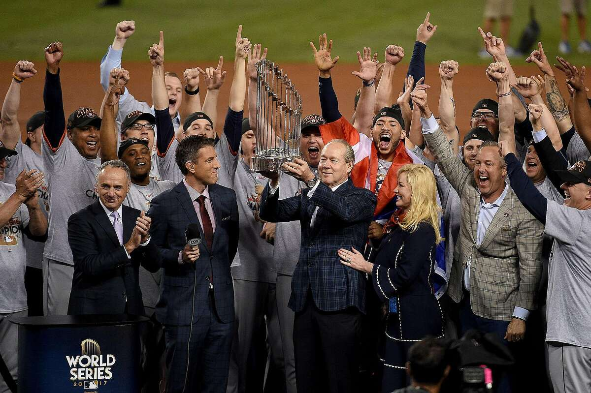 Houston Astros owner and chairman Jim Crane hoists the Commissioner's Trophy after the Astros defeated the Los Angeles Dodgers in Game 7 to win the World Series at Dodger Stadium in Los Angeles on November 1, 2017. (Kevork Djansezian/Getty Images/TNS)