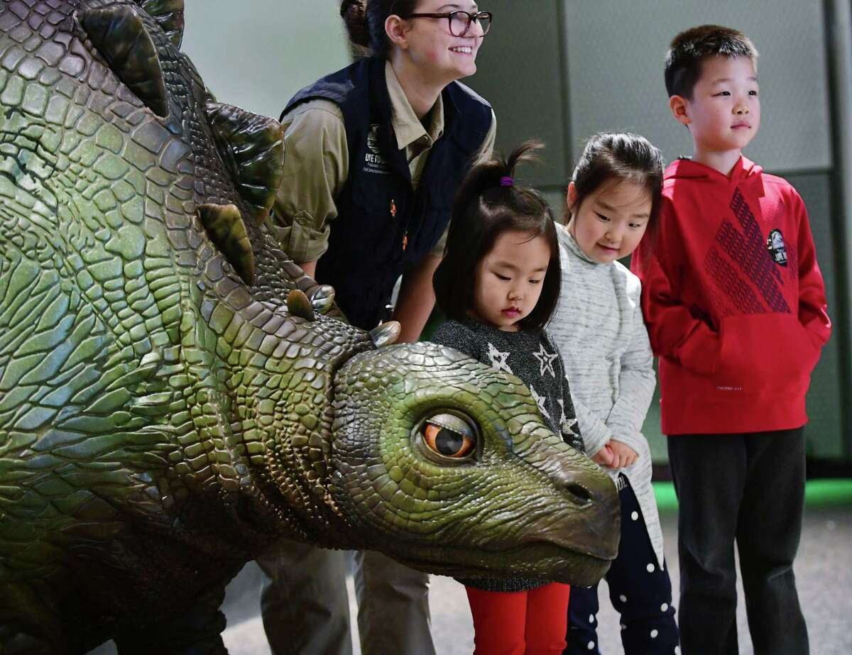 Steph Warrington of Feld Entertainment poses with children including Leah Choi, 4, Hannah Choi, 6, and Daniel Choi, 8, of Trumbull as Feld presents Jurassic World Live Tour event featuring Olive the animatronic baby Stegosaurus Friday, February 14, 2020, at Stepping Stones Museum for Children in Norwalk, Conn.