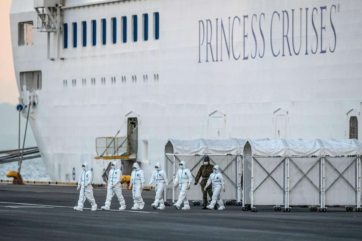 YOKOHAMA, JAPAN - FEBRUARY 10: Emergency workers in protective clothing exit the Diamond Princess cruise ship at Daikoku Pier where it is being resupplied and newly diagnosed coronavirus cases taken for treatment as it remains in quarantine after a number of the 3,700 people on board were diagnosed with coronavirus, on February 10, 2020 in Yokohama, Japan. 130 passengers are now confirmed to be infected with coronavirus as Japanese authorities continue treating people on board. The new cases bring the total number of infections to 156 in Japan, the largest number outside of China.