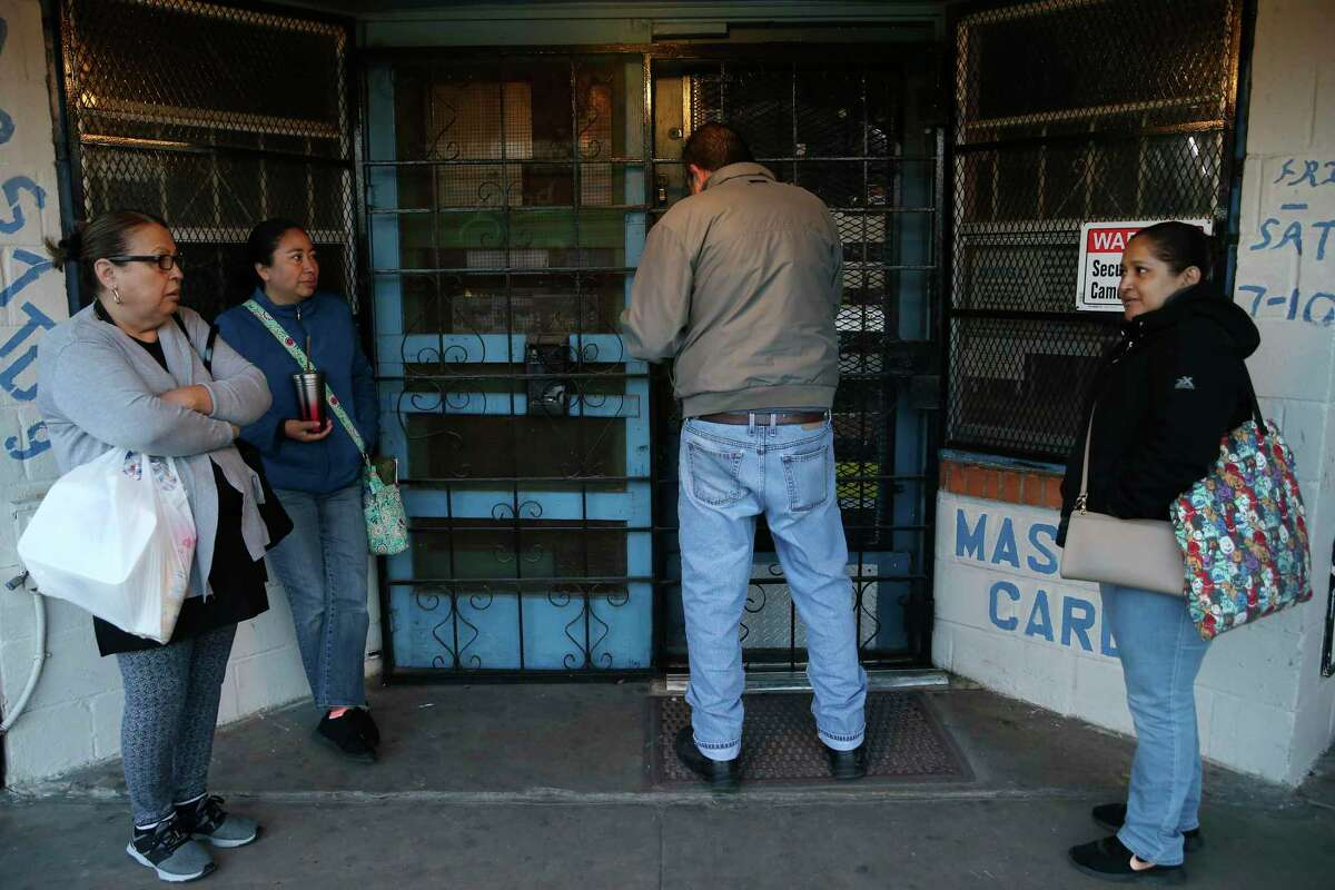 Reyna Castillo, 62, Oti Moreno, 40, and Maria Hernandez, 44, wait as Kenney's Food Store owner Al Mendoza opens the doors. The original store was established in 1886 on Laredo Street but moved decades later to the present location on Merida Street.