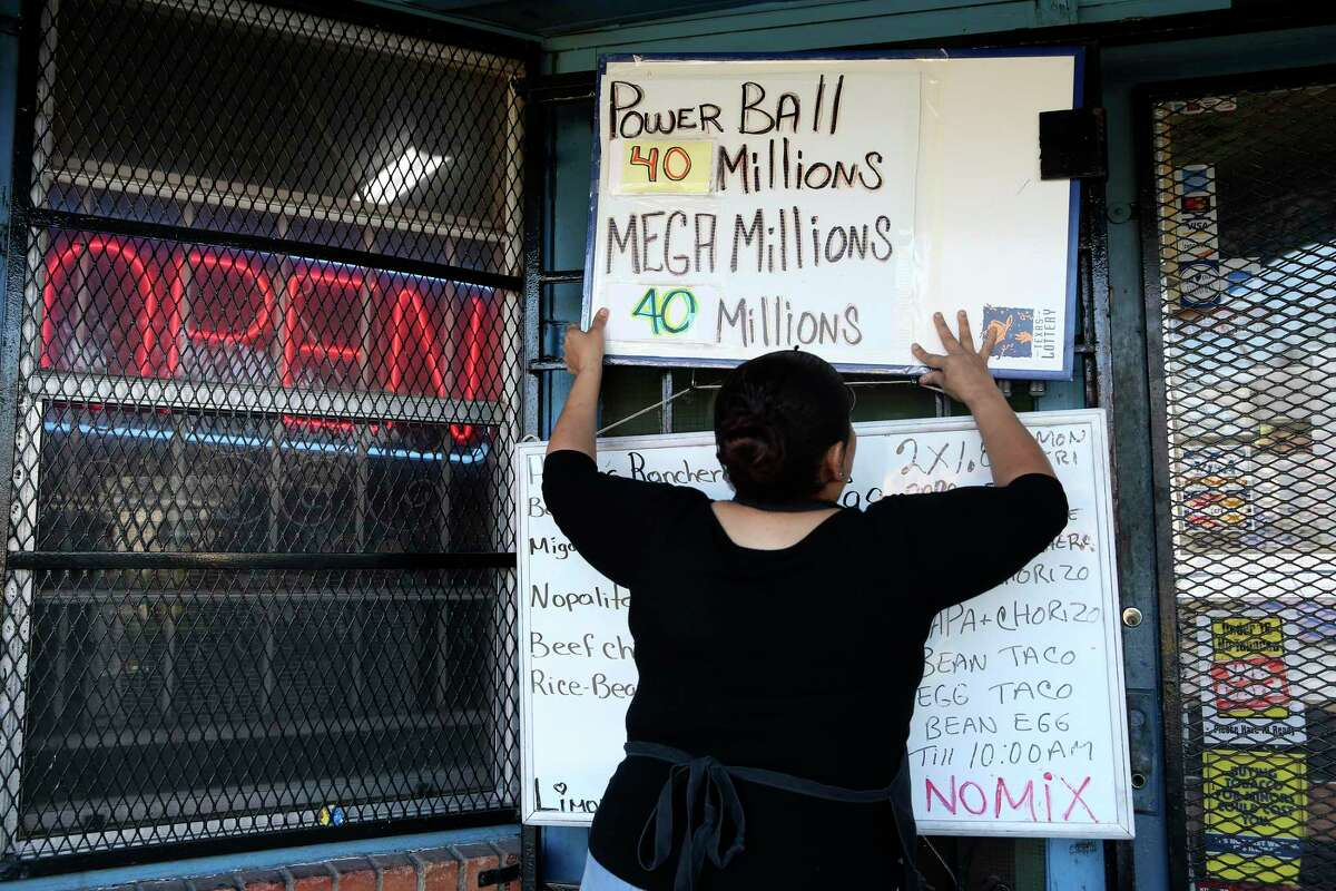 Maria Hernandez hangs the day's specials and lottery jackpots by the Kenney's entrance.