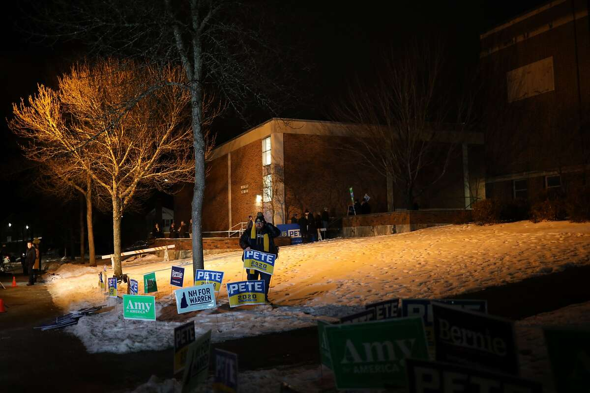 MANCHESTER, NEW HAMPSHIRE - FEBRUARY 11: A supporter of Democratic presidential candidate former South Bend, Indiana Mayor Pete Buttigieg places campaign signs before the opening of a polling station at Webster School February 11, 2020 in Manchester, New Hampshire. New Hampshire holds its first in the nation primary today. (Photo by Win McNamee/Getty Images)