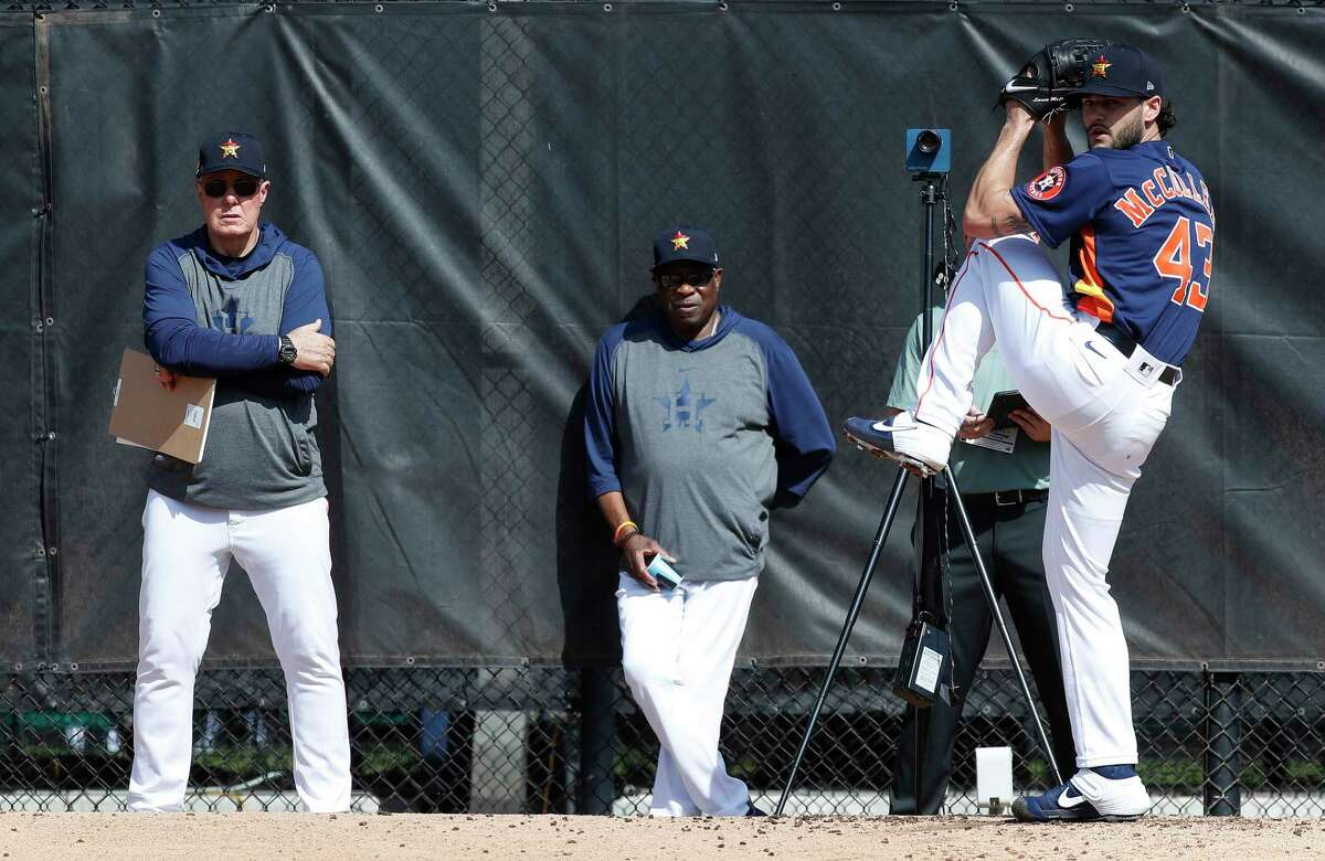 Astros pitching coach Brent Strom, left, and manager Dusty Bakerwatch as pitcher Lance McCullers Jr. (43) throws for the first time during spring training.