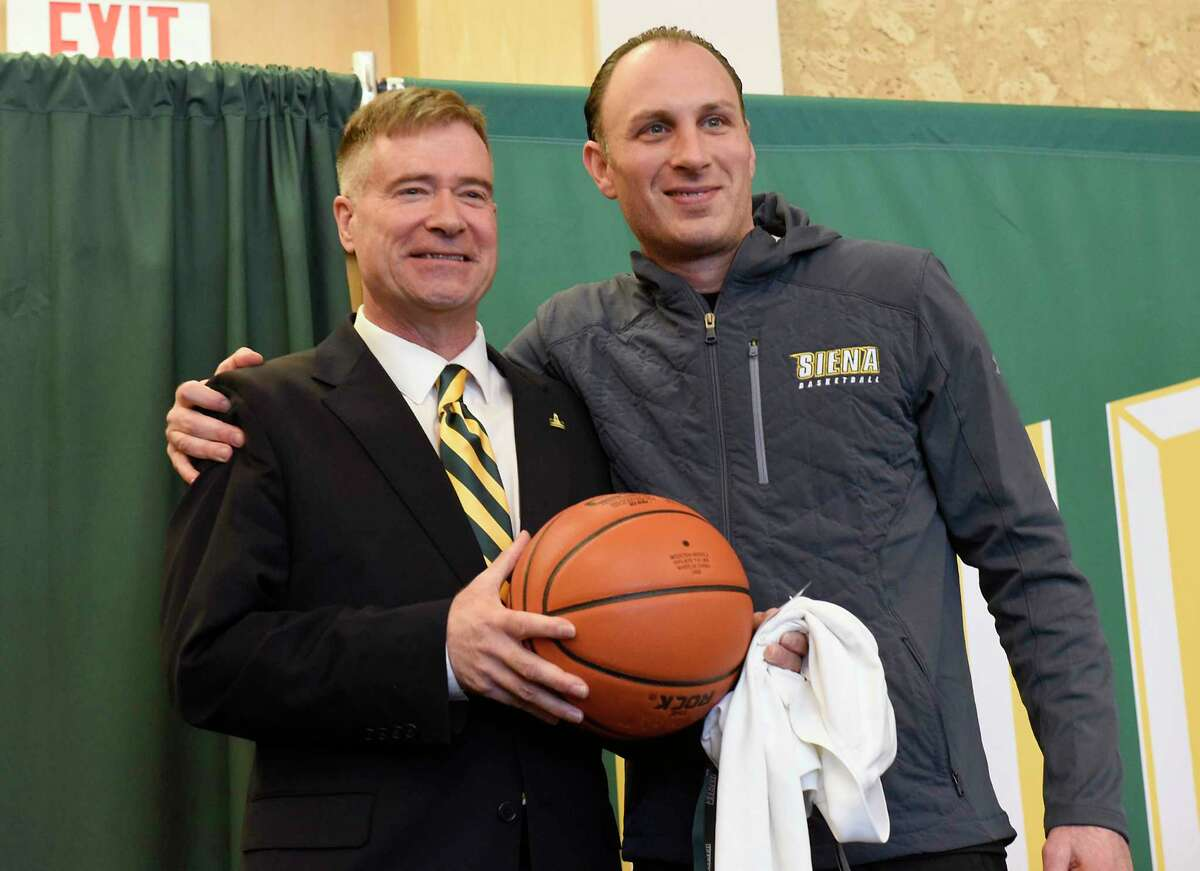 Carmen Maciariello, head coach men's basketball team, gives former U.S. Rep. Chris Gibson gifts as Siena College announces him as its 12th president at Siena College on Friday, Feb. 14, 2020 in Loudonville, N.Y. Gibson, Ph.D, graduated from Siena in the class of '86. (Lori Van Buren/Times Union)