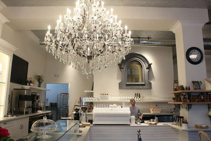 Maison Danel owner Danel de Betelu makes a latte in his new San Francisco tea salon, which is dominated by a large chandelier.
