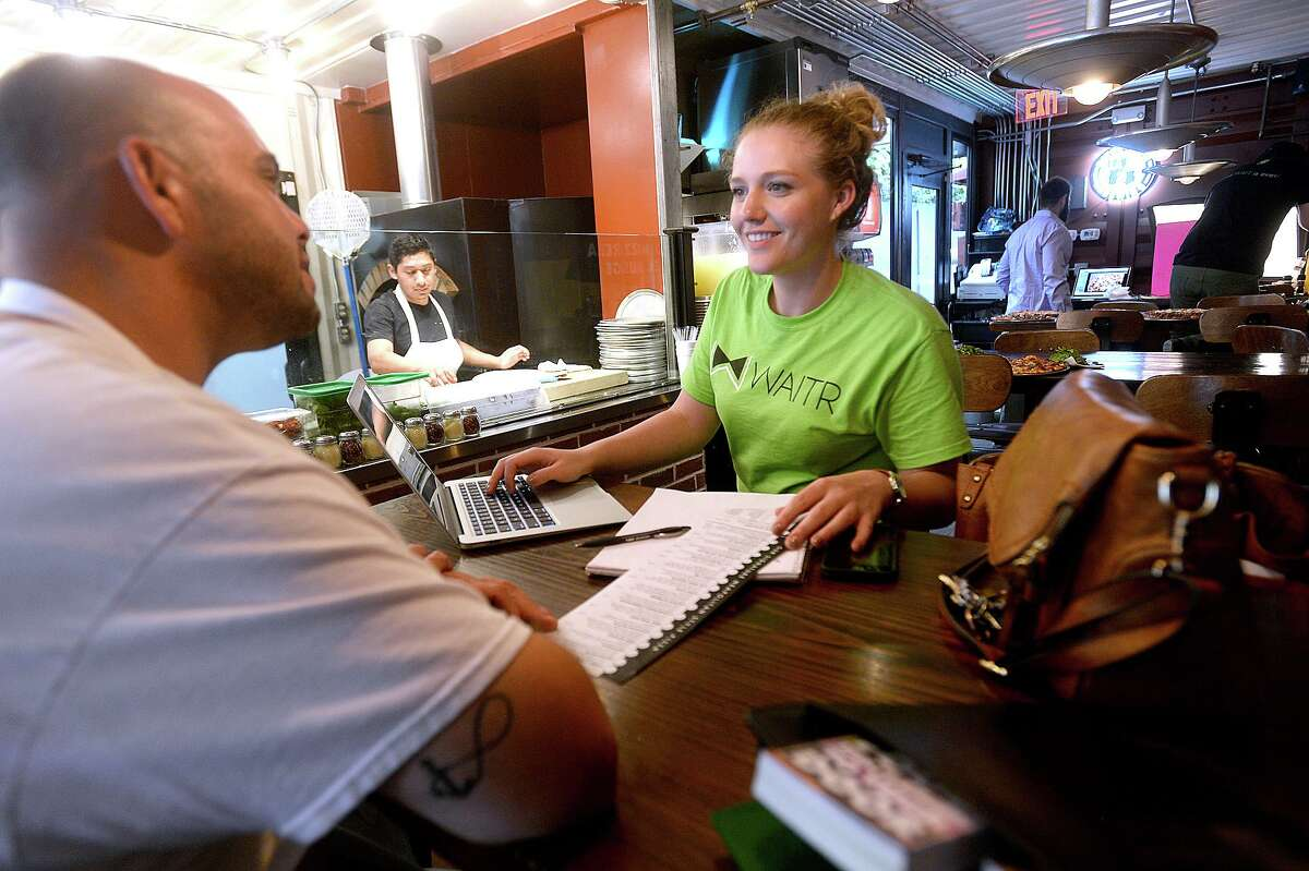 Shelby Hoffpauir, a restaurant success manager with Waitr, consults with Crown Pizza manager Kenneth Choate about the menu and text to be used in their listing on the food delivery business' app.