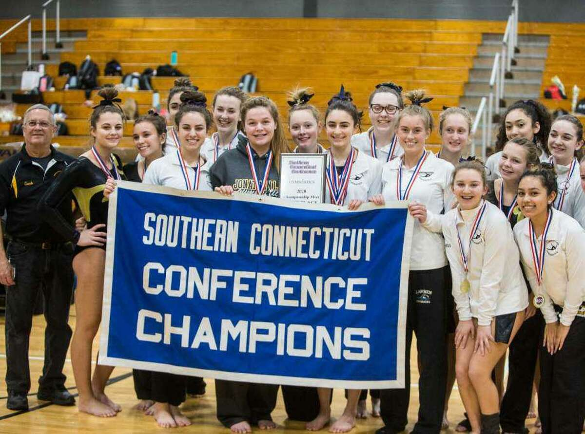 Jonathan Law gymnasts gather together with the banner designating coach Pat Simon's Lady Lawmen as 2020 Southern Connecticut Conference champions.
