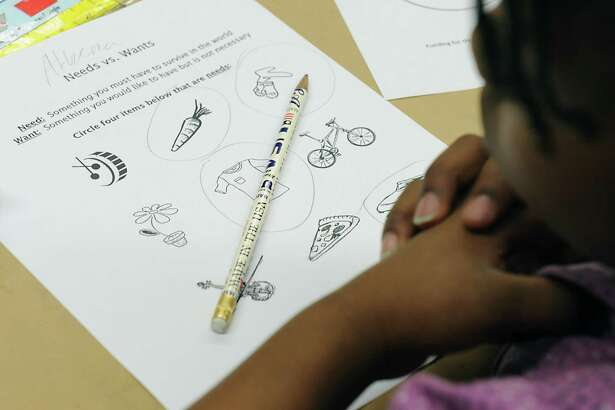 """Children are asked to circle objects they might need as apposed to objects they want during a """"Money Math: Saving, Spending & Sharing"""" financial literacy program at the Central Park International Magnet School in Schenectady, N.Y."""