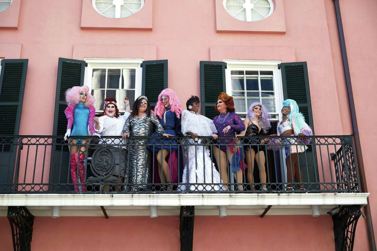 Some of New Orleans' best known drag queens pose on the balcony of Brennan's restaurant in the French Quarter. The image is from