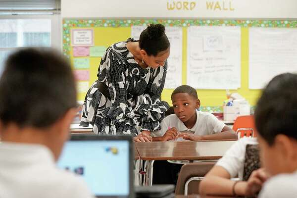 Second-grade teacher Stacy Ray helps students with their classwork at the Dallas ISD's Umphrey Lee Elementary School, one of the district's signature turnaround schools involved in the initiative known as Accelerating Campus Excellence, or ACE. District officials put hundreds of thousands of additional dollars into seven ACE campuses, which immediately showed significant academic and behavioral gains.