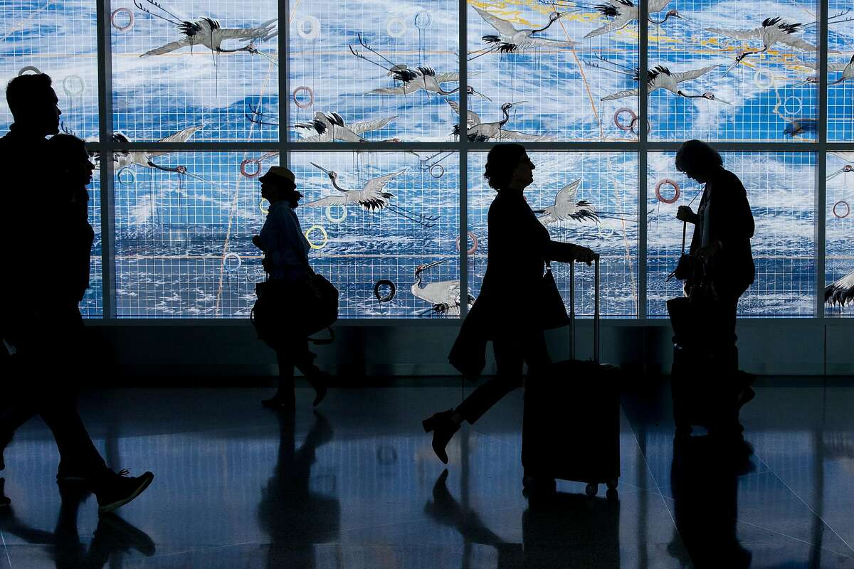 Travelers are silhouetted against a window art installation called Going Away, Coming Home by Hung Liu while making their way through Terminal 2 at Oakland International Airport in Oakland, Calif. Thursday, January 30, 2020. The airport has had a year of ups and downs, with large airlines such as Norwegian and JetBlue rerouting away from Oakland and to SFO, but at the same time Southwest has expanded its services out of Oakland to Hawaii, leaving the promise of even more travelers making their way through the terminals of Oakland International Airport.
