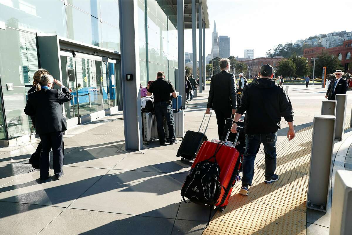 Passengers leave James R. Herman Cruise Terminal at Pier 27 after arriving from Hawaii on the Grand Princess in San Francisco on February 11, 2020.