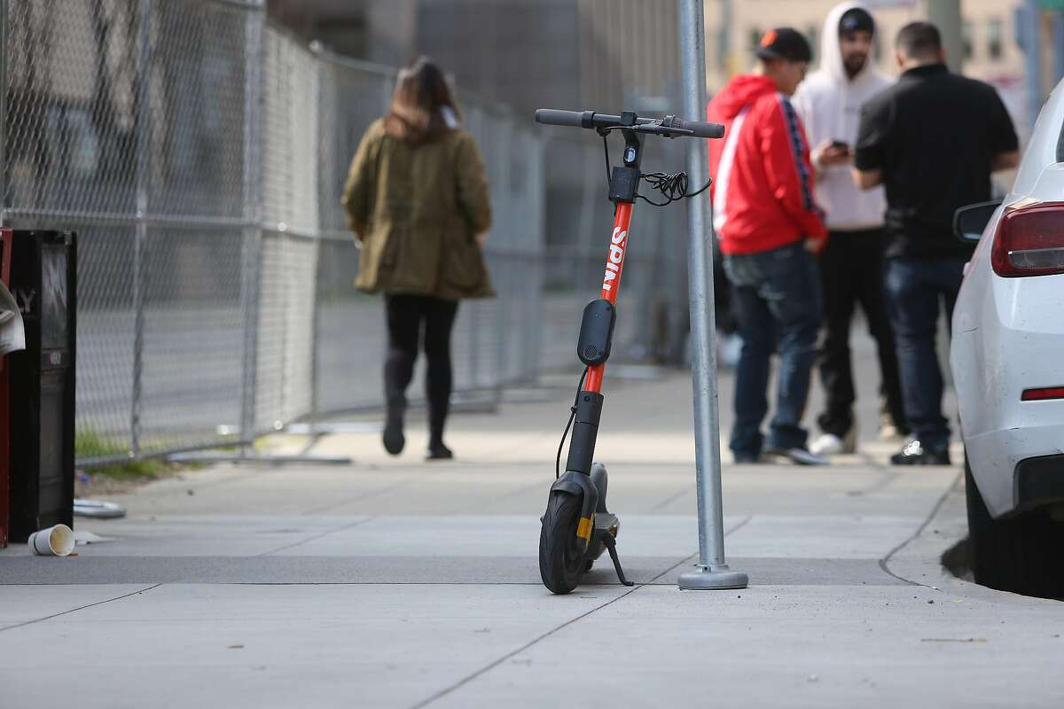 A scooter is seen locked to a sign post along Main Street on Friday, February 14, 2020 in San Francisco, Calif.