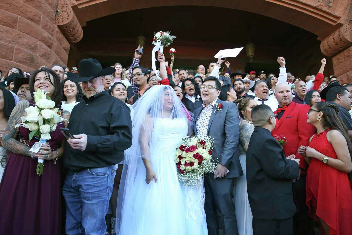 A cheer goes up as ceremonies start before couples exchange vows on the steps of the Bexar County Courthouse in a Valemntine's Day ceremony on Feb. 14, 2020.