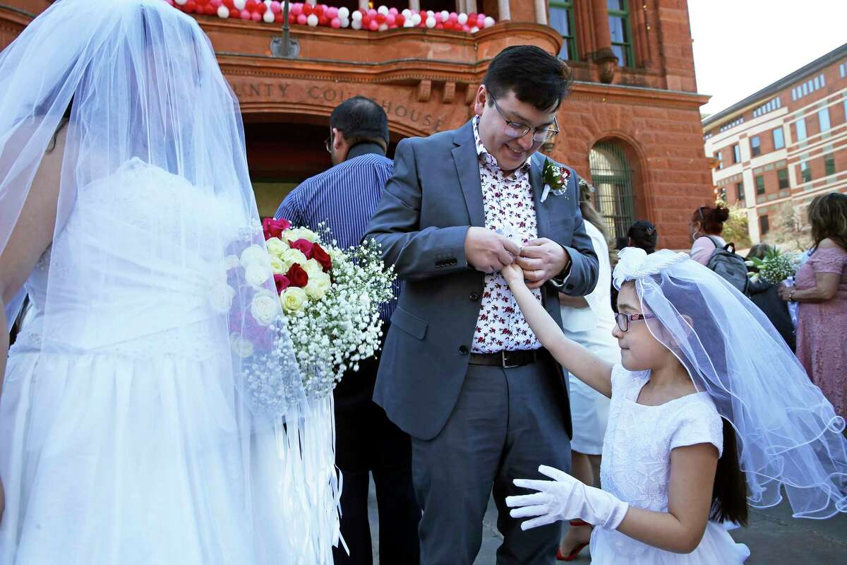 Anthony Pena fits his daughter Sophia with white gloves while the bride, Frances Mendoza, waits before couples exchange vows on the steps of the Bexar County Courthouse in a Valemntine's Day ceremony on Feb. 14, 2020.