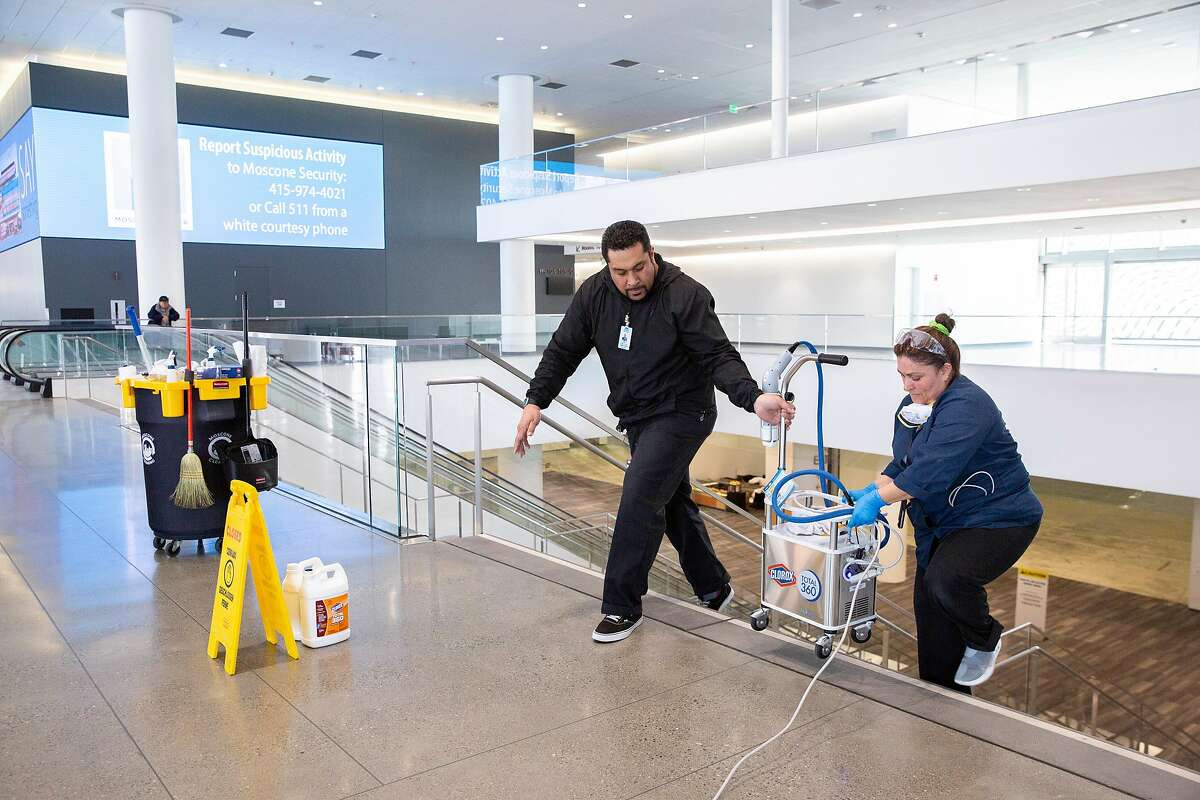 From left: Tipeti Paini helps Evelin Rivera move the electrostatic cleaner at Moscone Center South, Friday, Feb. 14, 2020, in San Francisco, Calif.