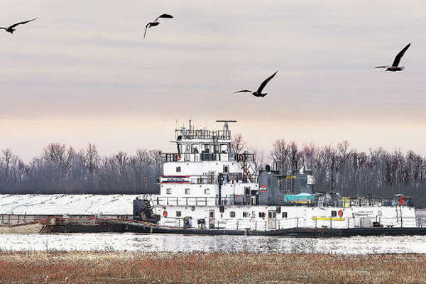 A towboat pushes its barges down a low Mississippi River headed for the Melvin Price Locks and Dam 26 on Friday. The river is being kept low in anticipation of higher volumes of water this spring, with the National Weather Service reporting a high likelihood of spring flooding.