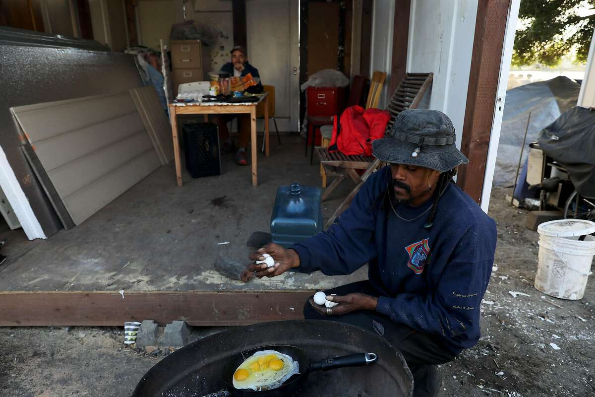 Ayat Jalal, 46, co-founder of First They Came For the Homeless, fries eggs as he makes dinner at a tiny home community called the Right to Exist Curbside Community, located off of E. 12th St. in Oakland, Calif., on Tuesday, February 4, 2020. Jalal has lived at the site since MLK Day. Currently there are eight tiny homes and one cob house at the location. Oakland and Berkeley city councils have committed to building self governing encampments to address the homeless crisis in their cities. But neither city really has put any full proof plan forward as to what a self governing is and how it should function. Berkeley is one step closer by directing staff to identify locations. Oakland however, is not. Instead, advocates in Oakland have resorted to building tiny home villages throughout the city -- unsanctioned -- as an example of what a self-governing encampment should look like.