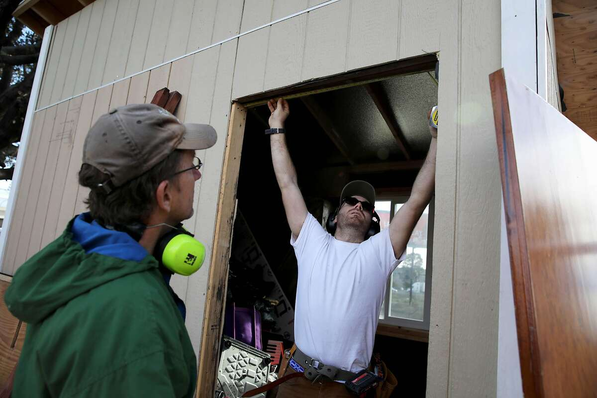 """Paul Brumbaum, a carpenter, left, and Gabriel Kahn make measurements before installing a door for a tiny home in a community called the Right to Exist Curbside Community, located off of E. 12th St. in Oakland, Calif., on Tuesday, February 4, 2020. Currently there are eight tiny homes and one cob house at the location. """"Obviously, the first thing people need when they get into this situation is a safe place for themselves and a door they can lock so their possessions are not gonna be walking off and they can put their lives back together,"""" Brumbaum said. """"What we're really trying to create here is not just tiny homes but a community, and this is the first communal space that's been created."""" Oakland and Berkeley city councils have committed to building self governing encampments to address the homeless crisis in their cities. But neither city really has put any full proof plan forward as to what a self governing is and how it should function. Berkeley is one step closer by directing staff to identify locations. Oakland however, is not. Instead, advocates in Oakland have resorted to building tiny home villages throughout the city -- unsanctioned -- as an example of what a self-governing encampment should look like."""