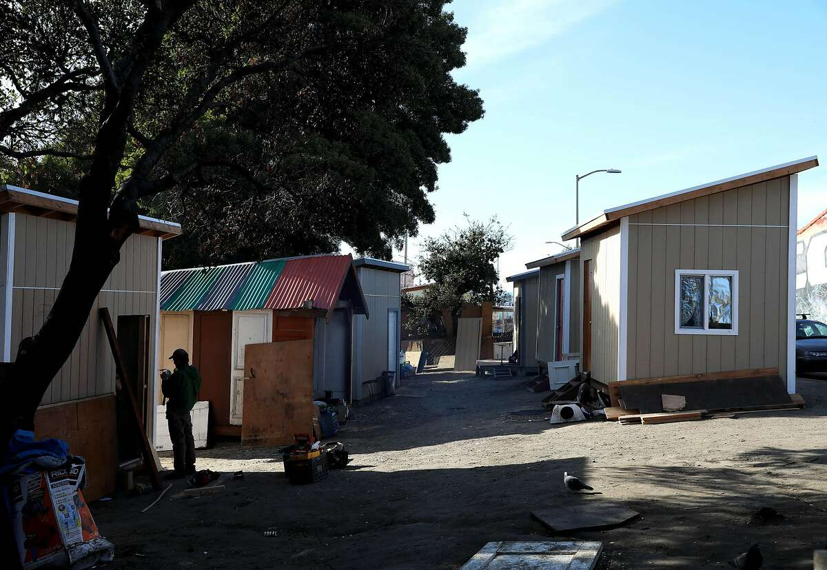 """Paul Brumbaum, a carpenter, installs a door for a tiny home in a community called the Right to Exist Curbside Community, located off of E. 12th St. in Oakland, Calif., on Tuesday, February 4, 2020. Currently there are eight tiny homes and one cob house at the location. """"Obviously, the first thing people need when they get into this situation is a safe place for themselves and a door they can lock so their possessions are not gonna be walking off and they can put their lives back together,"""" Brumbaum said. """"What we're really trying to create here is not just tiny homes but a community, and this is the first communal space that's been created."""" Oakland and Berkeley city councils have committed to building self governing encampments to address the homeless crisis in their cities. But neither city really has put any full proof plan forward as to what a self governing is and how it should function. Berkeley is one step closer by directing staff to identify locations. Oakland however, is not. Instead, advocates in Oakland have resorted to building tiny home villages throughout the city -- unsanctioned -- as an example of what a self-governing encampment should look like."""