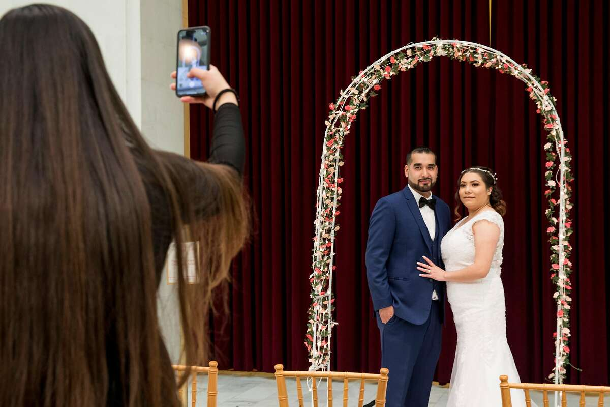 A newly wed couple take pictures under a decorated arch in the North Light Court of San Francisco City hall in San Francisco, Calif. Friday, February 14, 2020. City Hall has hosted their Valentine's Day celebration for four years, with over 140 couples reserved to tie the knot under the rotunda on the romantic date.