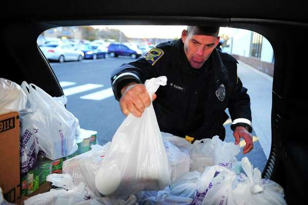 "Ansonia police officer Mike Barry loads donated food into the back of a Jeep from Fitzpatrick Chrysler Jeep of Ansonia during the department's annual ""Stuff A Jeep"" Holiday Food and Toy Drive at the Stop & Shop in Ansonia."