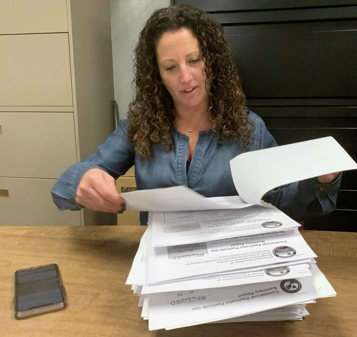Tara Cook-Littman of Fairfield has researched the golf course and agricultural applications in Connecticut of the controversial pesticide chloropyifos, which is banned in Europe and banned in the United States for most household use. She is shown with files at the offices of DEEP, the state Department of Energy and Environmental Protection.
