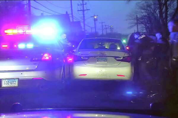This Jan. 15, 2020, still image from dashboard camera video released via the Connecticut State Police shows officers surrounding a vehicle stopped in West Haven, Conn., following a high-speed chase along Interstate 95 after Mubarak Soulemane, 19, had carjacked the vehicle in Norwalk, Conn. Trooper Brian North, left, fatally shot Soulemane sitting in the driver's seat and displaying a knife, after troopers tried to use a stun gun but it didn't work, state police said. Clergy and relatives of Soulemane have called for the trooper be sent home on suspension and are asking for more de-escalation training. (Connecticut State Police via AP)