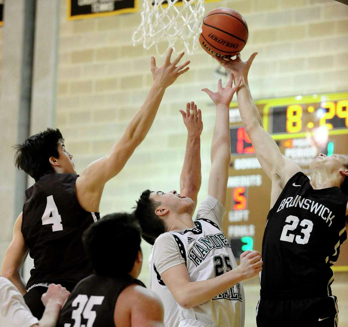 Brunswick's Logan Galletta (4) and Colin Mulshine (23) fights for the rebound against Hamden Hall Tyler Callahan (25) in the first half of an FAA boys basketball game at Brunswick School on Feb. 14, 2020 in Greenwich Connecticut. Hamden Hall defeated Brunswick 59-58.