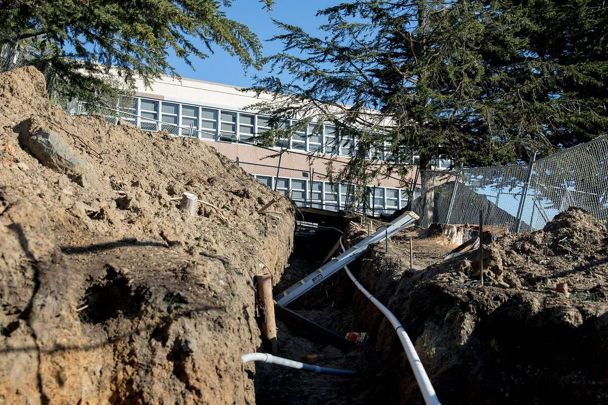 Dirt and construction are seen behind a fenced-off portion of the walkways near Cloud Hall after an irrigation line was found to be in need of repairs at City College of San Francisco's Ocean Campus in San Francisco, Wednesday, February 12, 2020. City College of San Francisco administration is asking voters to approve Prop A, an $845 million bond measure for building repairs, in the upcoming March election.