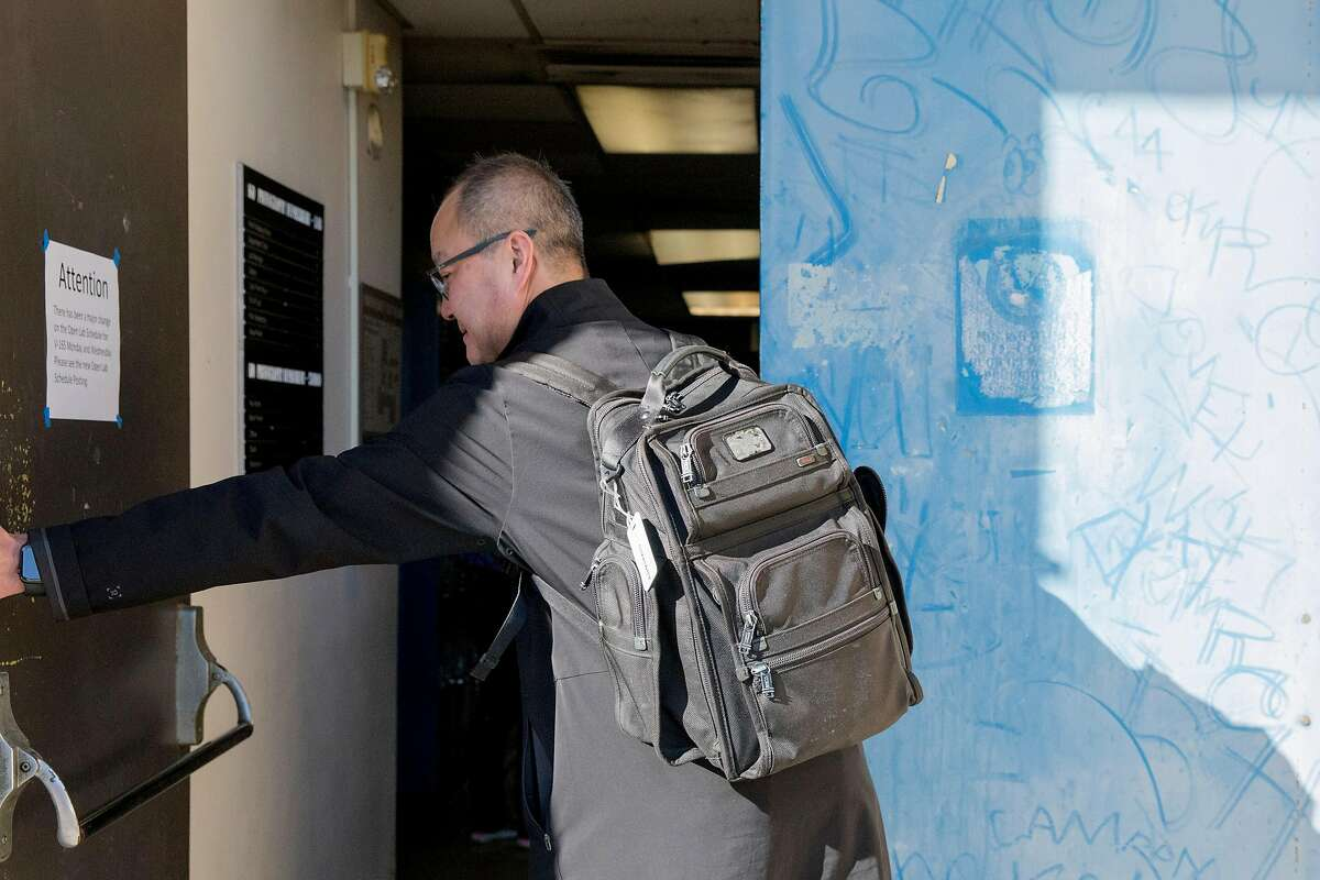 Dr. James Sohn, Senior Vice Chancellor of Facilities and Capital Planning, opens a worn-out door covered in graffiti while entering the Visual Arts building at City College of San Francisco's Ocean Campus in San Francisco, Wednesday, February 12, 2020. City College of San Francisco administration is asking voters to approve Prop A, an $845 million bond measure for building repairs, in the upcoming March election.