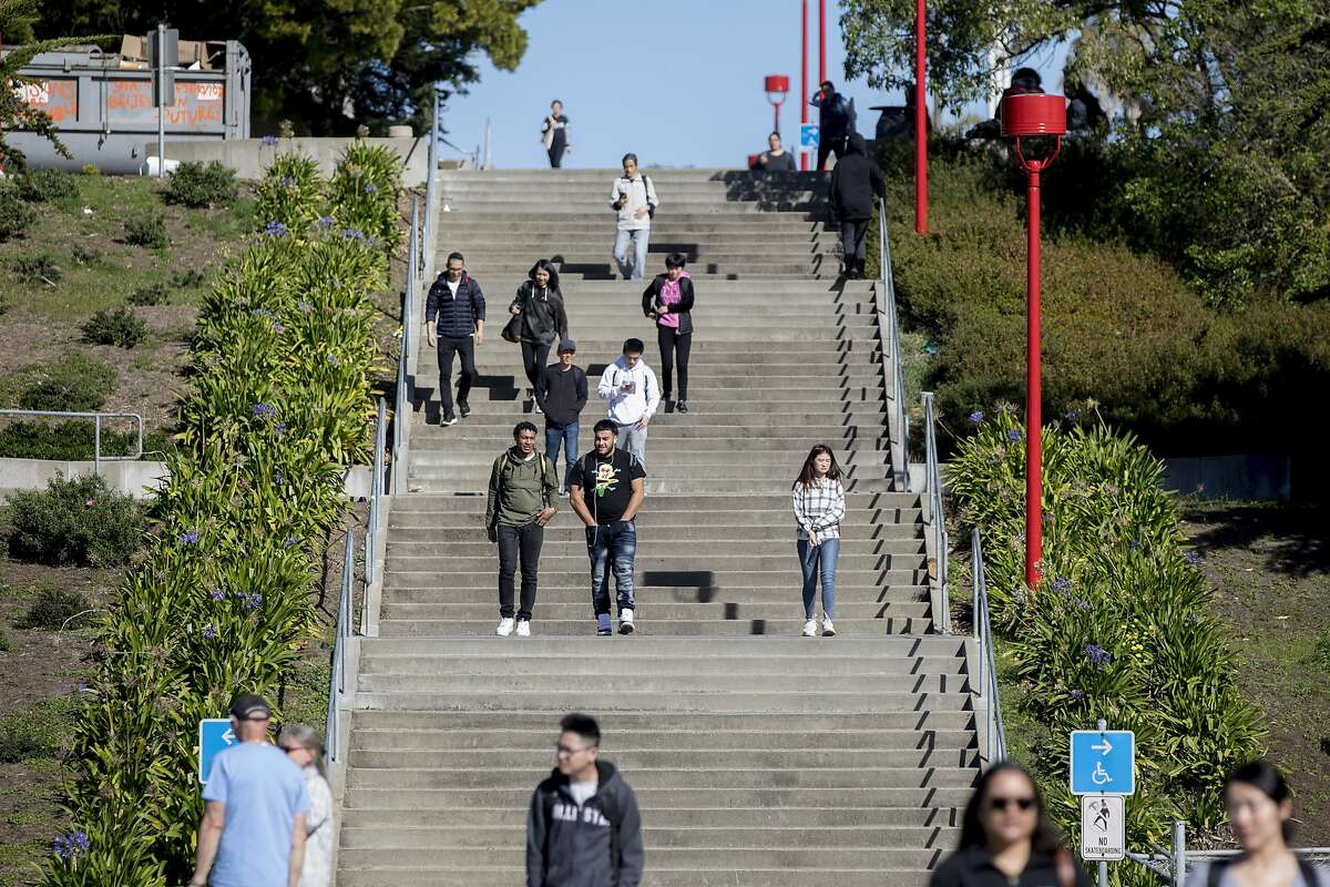 Students descend the staircase leading from Science Hall at City College of San Francisco's Ocean Campus before the pandemic last year. On Monday, faculty members agreed to pay cuts to save hundreds of instructors from being laid off and their classes from being eliminated.
