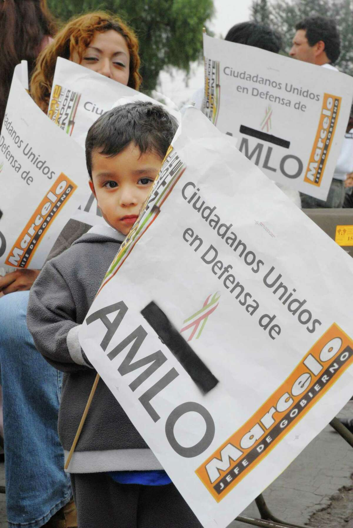 """A child holds a sign in support of Andres Manuel Lopez Obrador during a rally in the working class Iztapalapa borough of Mexico City on Thursday, Nov. 16, 2006. The rally was one of dozens nationwide aimed at firing up supporters ahead of Lopez Obrador's """"swearing-in"""" as the """"legitimate president of Mexico"""" on Nov. 20."""