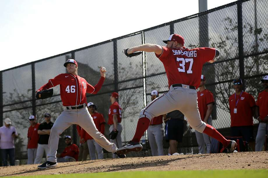 Nationals pitcher Stephen Strasburg (right, throwing next to left-hander Patrick Corbin on Friday) said Washington used new catcher's signals during the World Series and changed them during games to prevent the Astros from cheating. Photo: Jeff Roberson / Associated Press