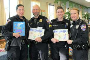 Read Aloud Day was held at area schools on Feb. 12, hosted by the Northwest CT Chamber of Commerce. Above, Torrington police officers show their books before heading into a local classroom to read.