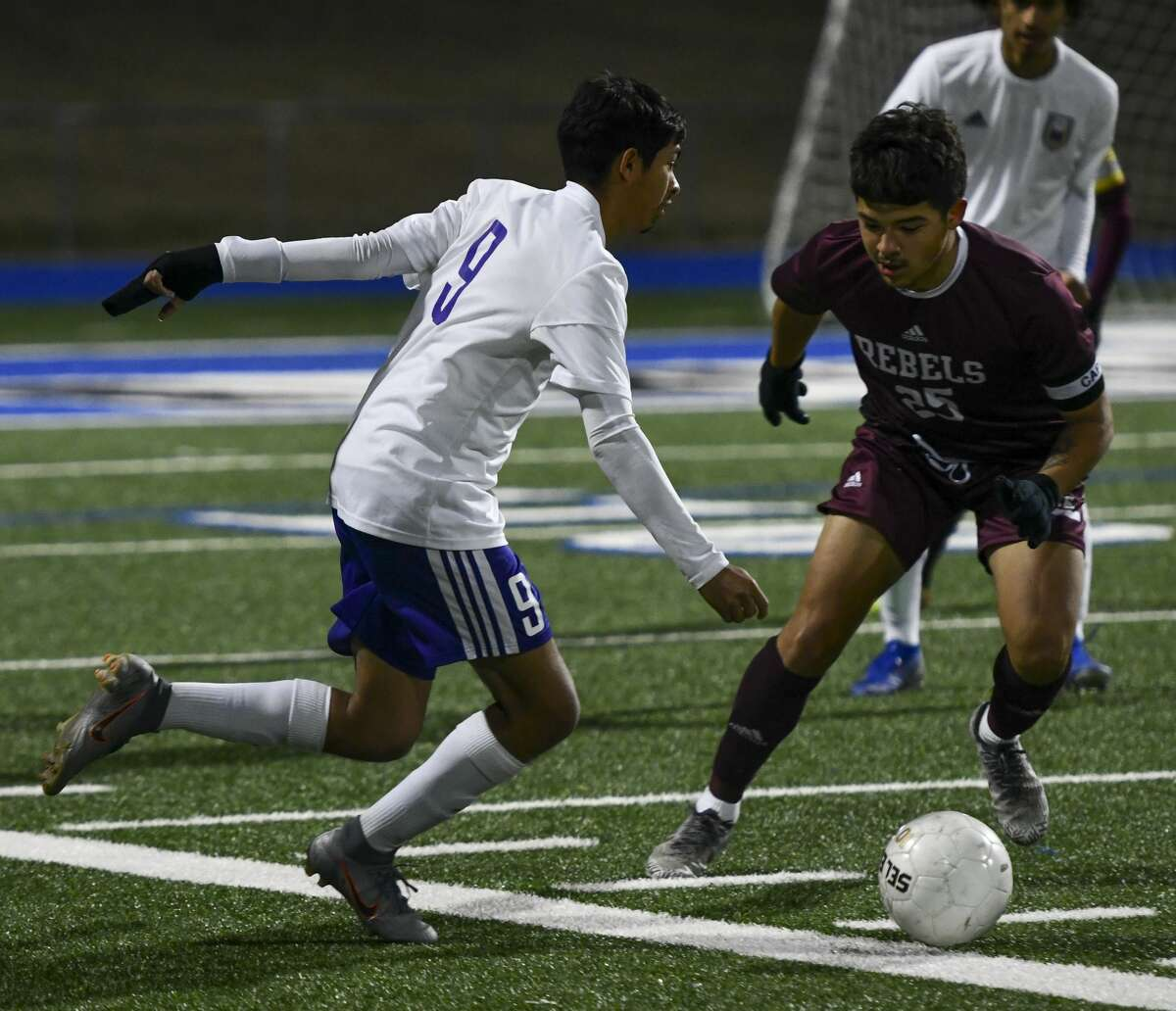 Midland High's Jordan Alfaro (9) looks to pass the ball as Lee's Marco Jurado attempts to steal the ball Friday, Feb. 14, 2020 at Grande Communications Stadium.