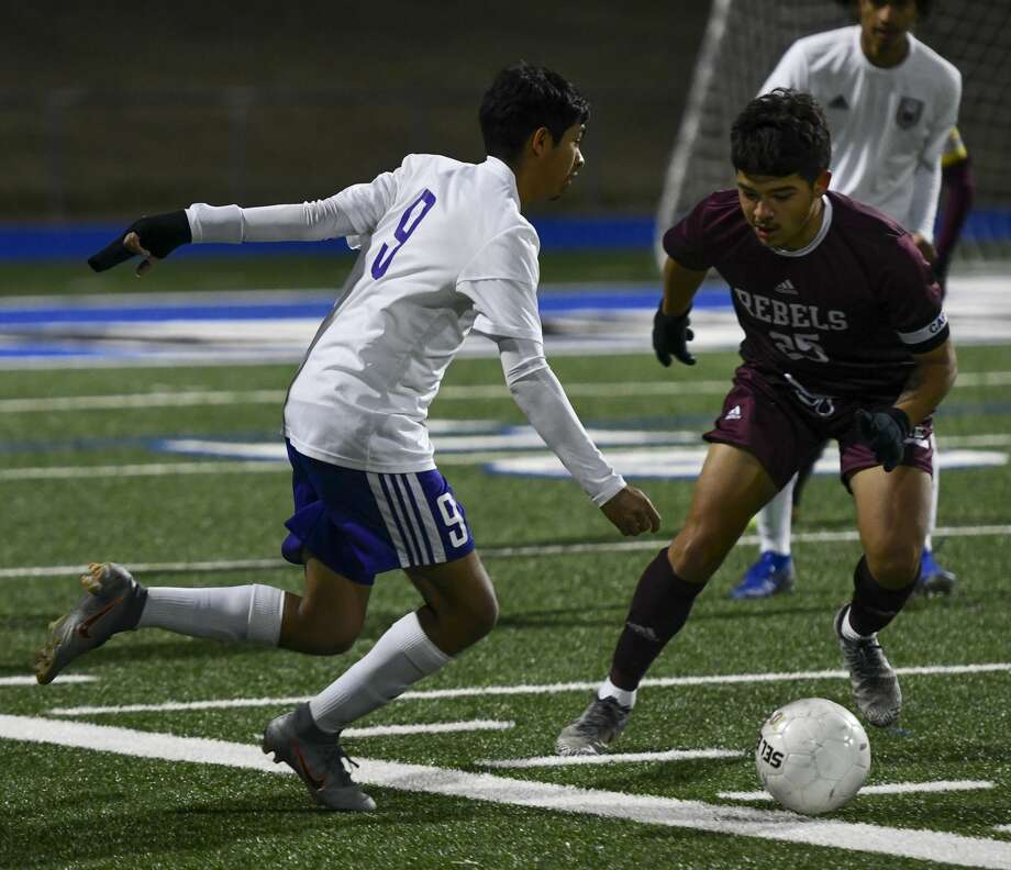 Midland High's Jordan Alfaro (9) looks to pass the ball as Lee's Marco Jurado attempts to steal the ball Friday, Feb. 14, 2020 at Grande Communications Stadium. Photo: Jacy Lewis/Reporter-Telegram
