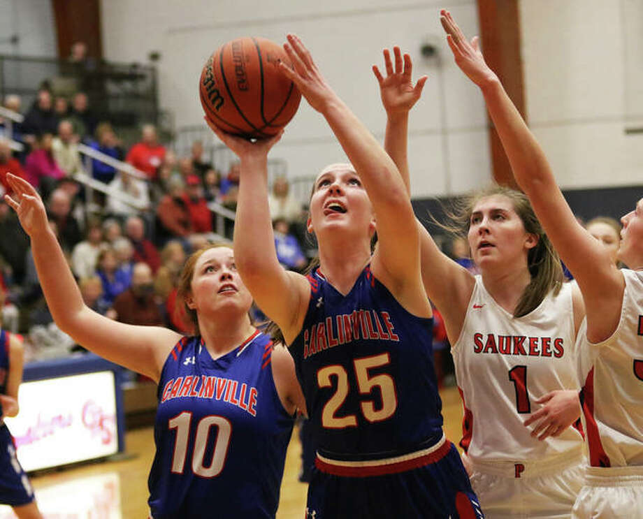 Carlinville's Sarah DeNeve (25) goes back up to score off a rebound in front of the Cavs' Elise Baker (10) and Pittsfield's Katie Cox (1) in the first half Friday night in the title game of the Carlinville Class 2A Regional. Photo: Greg Shashack | The Telegraph