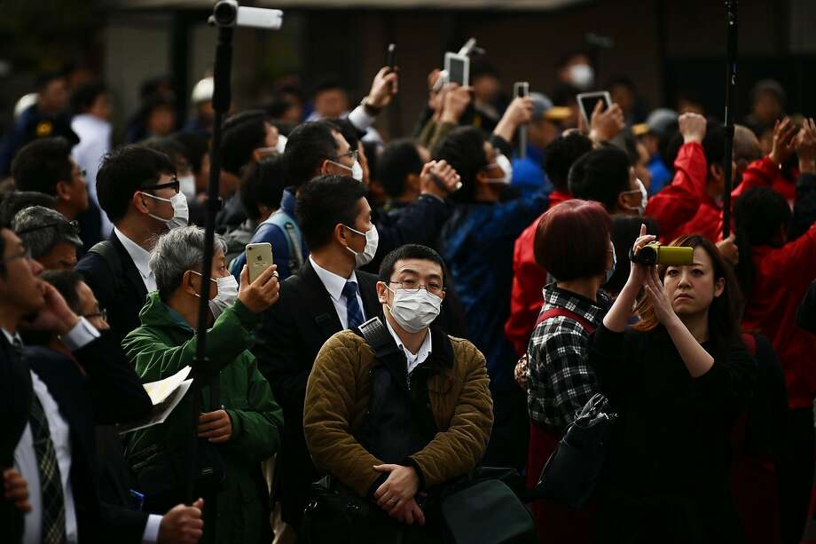 People wore facemasks to guard against the coronavirus epidemic during a rehearsal of the Tokyo 2020 Olympics torch relay in Tokyo on Saturday. Photo: Charly Triballeau / AFP Via Getty Images