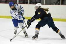 Darien's Kelly Raymond (11) takes a shot while Sinsbury's Anna Kahl defends during a girls ice hockey game at the Darien Ice House on Tuesday, Jan. 28, 2020.