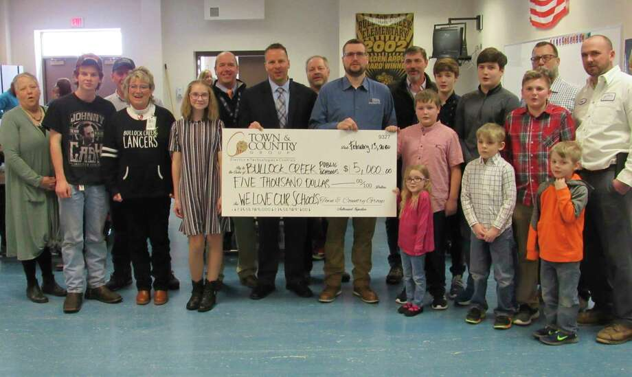 Representativesof theTown& County Group visitedBullock Creek Elementary School on Thursday to present a $5,000 check to pay off the school's lunch account deficit.(Mitchell Kukulka/Mitchell.Kukulka@mdn.net)