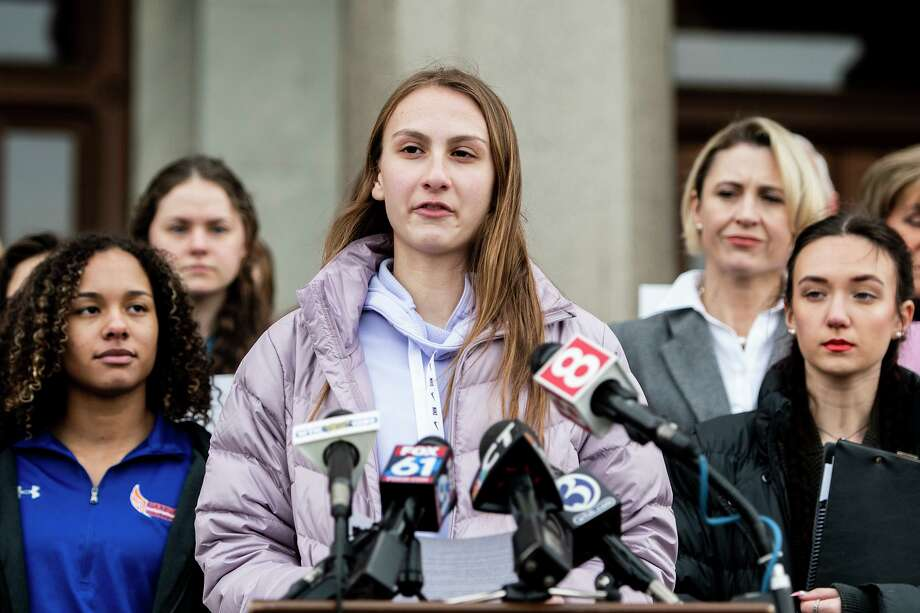 Canton High School senior Chelsea Mitchel speaks during a press conference with Alanna Smith, Danbury High School sophomore, to her left and Selina Soule, Glastonbury High School senior, to her right at the Connecticut State Capitol Feb. 12. The families of these three high school athletes have filed a federal lawsuit against the Connecticut Association of Schools and multiple school districts alleging discrimination. The athletes say they lost out on top finishes and possible scholarship opportunities because a statewide policy allows transgender athletes to compete against cisgender girls. Photo: Kassi Jackson / Tribune News Service / Hartford Courant