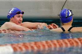 Olivia Theall of Friendswood talks to teammate Leslie Sisung after the Class 5A girls 100-yard butterfly at the UIL State Swimming & Diving Championships at the Lee & Joe Jamail Texas Swimming Center, Saturday in Austin. Theall and Sisung won the gold and bronze medals, respectively, in the event.