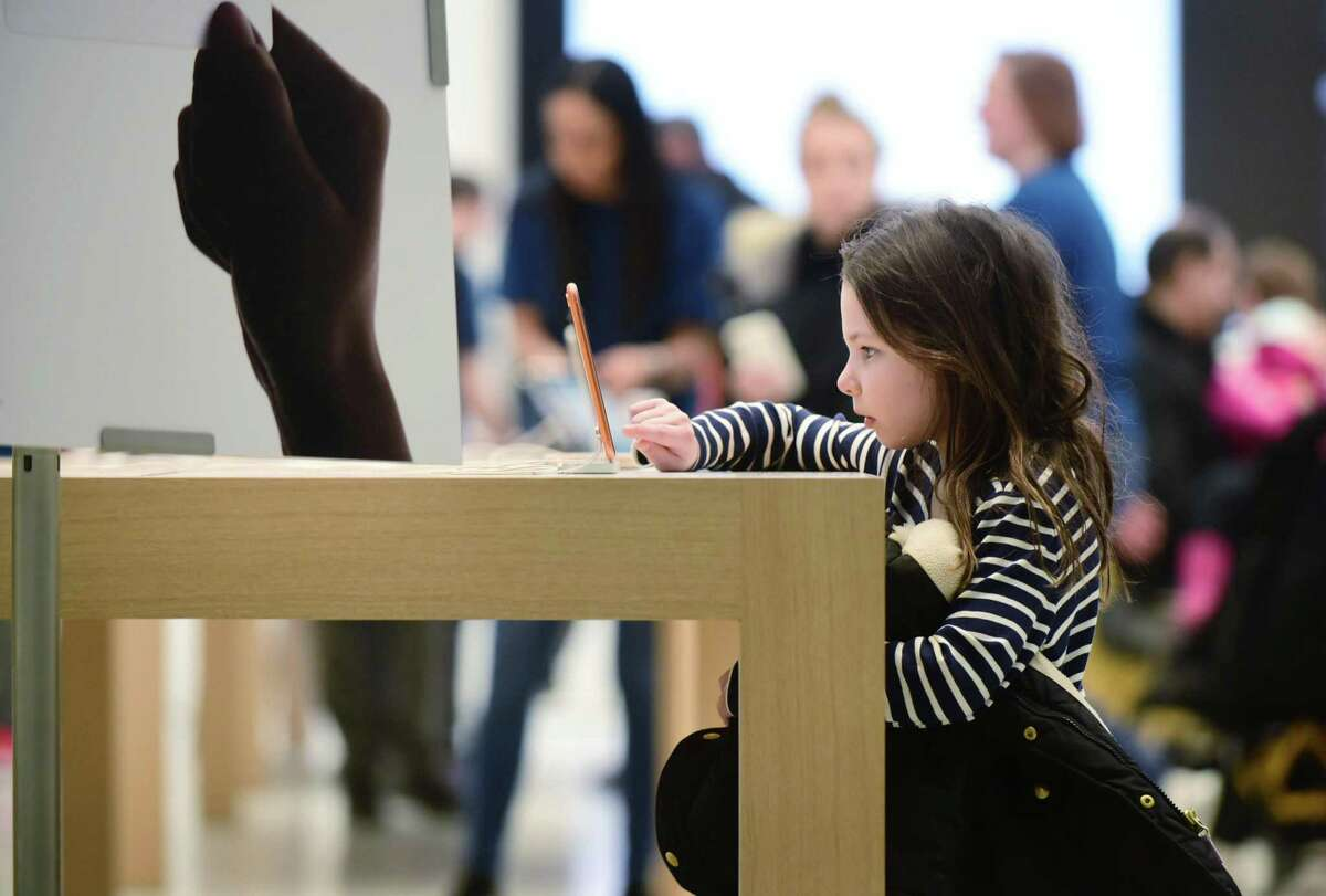 Six-year-old Maggie McGarvey,6, looks at an iPhone as Apple opens a new store at the SoNo Collection mall Saturday, February 15, 2020, in Norwalk, Conn.
