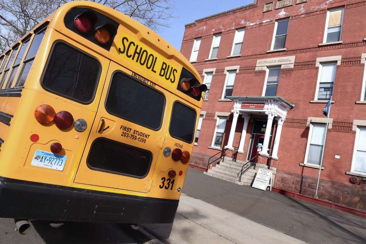 A bus waits to pick up children at the end of the school day at St. Francis & St. Rose of Lima School in New Haven on Feb. 12, 2020.